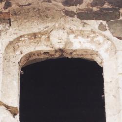 Fenêtre sur cour ornée d'un masque grimaçant.